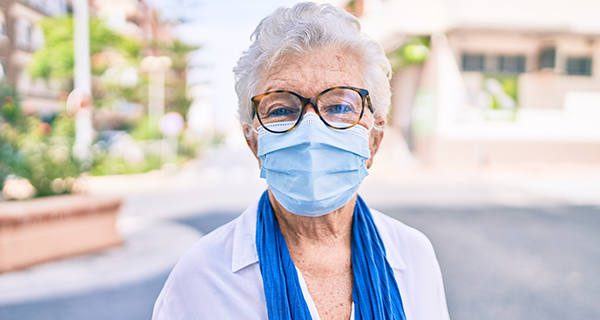 Senior woman with mask on smiling
