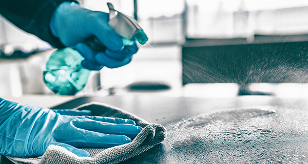 Spray bottle and cloth cleaning a hard surface